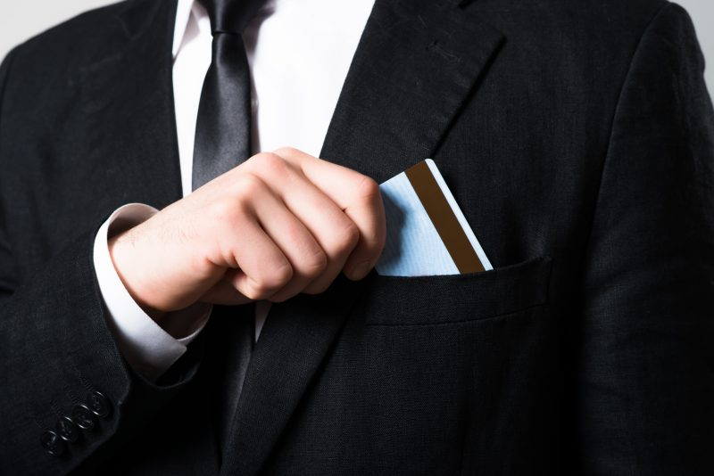 businessman put or take out credit card in pocket, close up